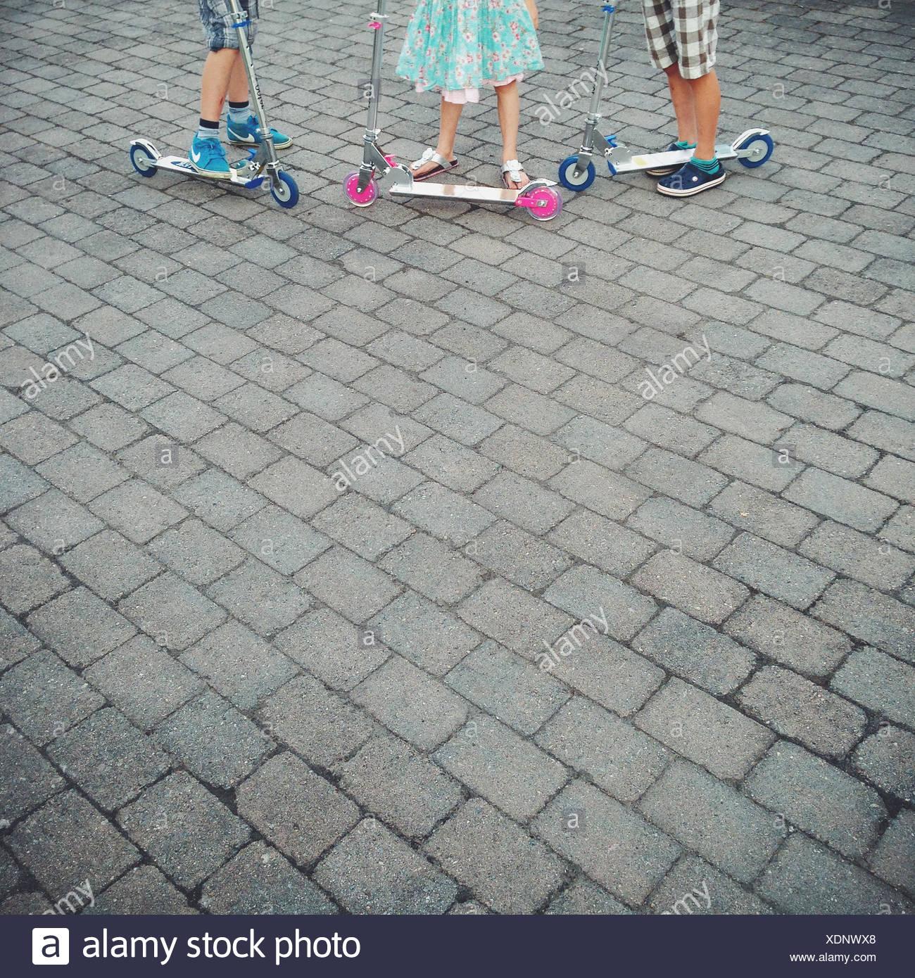 Close up of children (10-11, 12-13) debout à côté d'un scooter Photo Stock