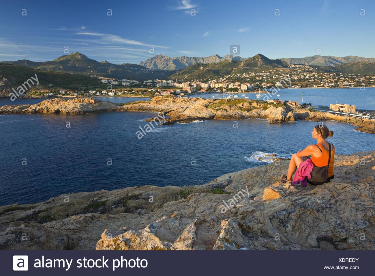 La France, la Corse, L'Ile Rousse, rock côte, femme, relaxation, vue de dos, Photo Stock