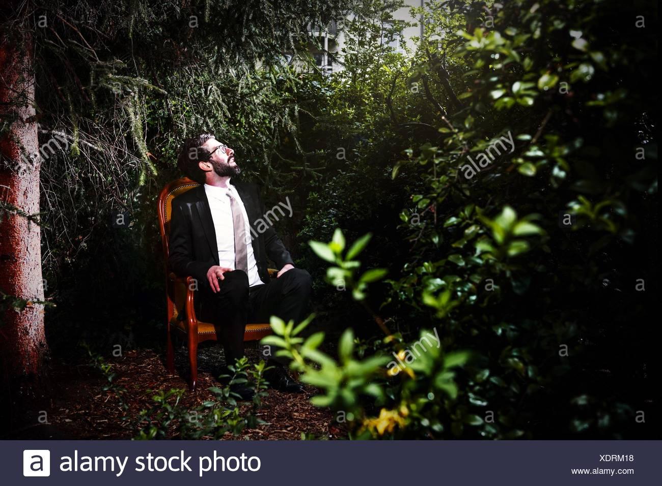 Costume homme assis sur une chaise dans la cour, tout en regardant vers le haut Photo Stock