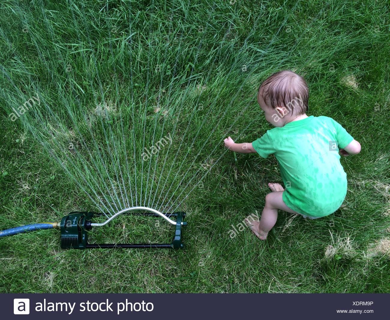 Portrait de l'enfant jouant par sprinkleurs On Grassy Field Photo Stock