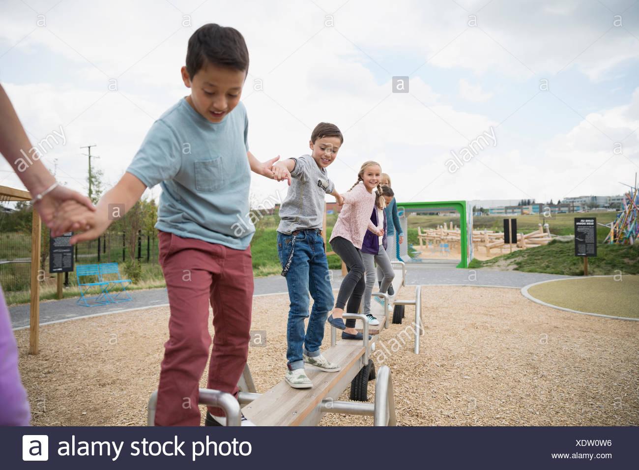 Les enfants en équilibre sur une balançoire à l'aire de jeux Photo Stock