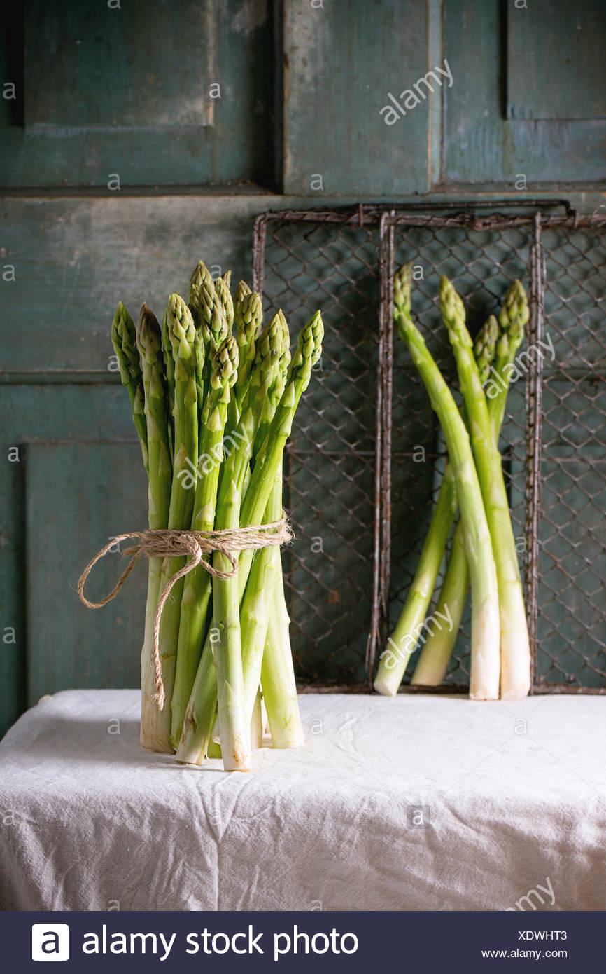 Ensemble d'asperges vertes sur nappe blanche avec fond en bois turquoise. Atmosphère rustique foncé Banque D'Images