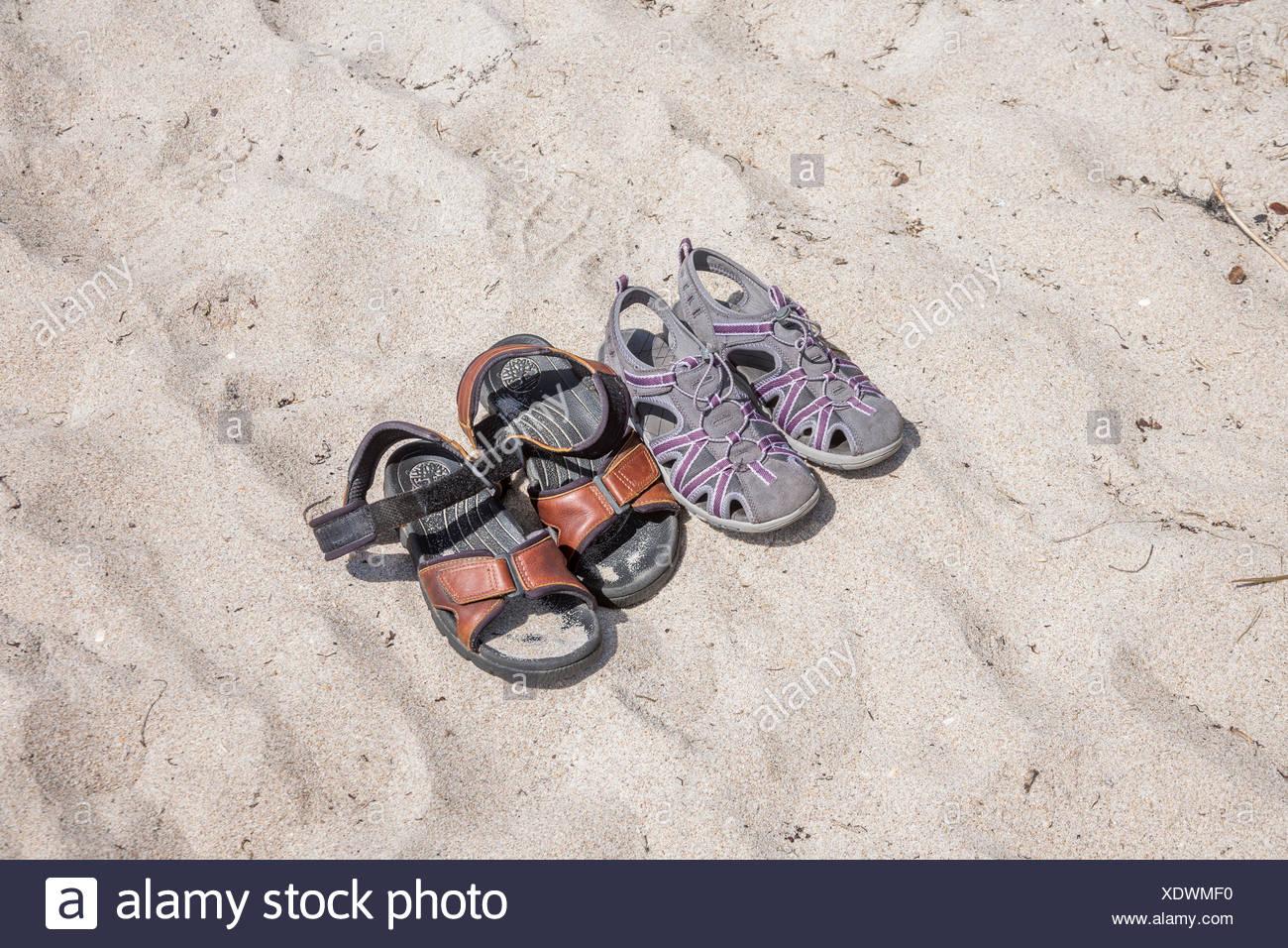 Deux paires de sandales sur le sable à la plage. Photo Stock