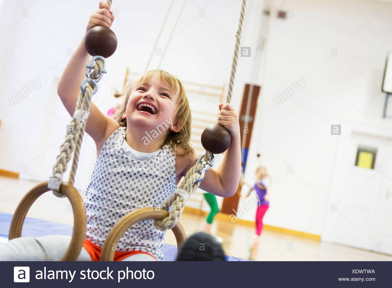 Anneaux de gymnastique fille sur l'école de hall Photo Stock