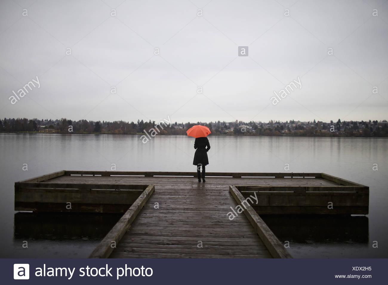 Une femme en tout noir et tenant un parapluie orange se dresse sur le bord d'un quai sur un jour nuageux et gris à Seattle Photo Stock