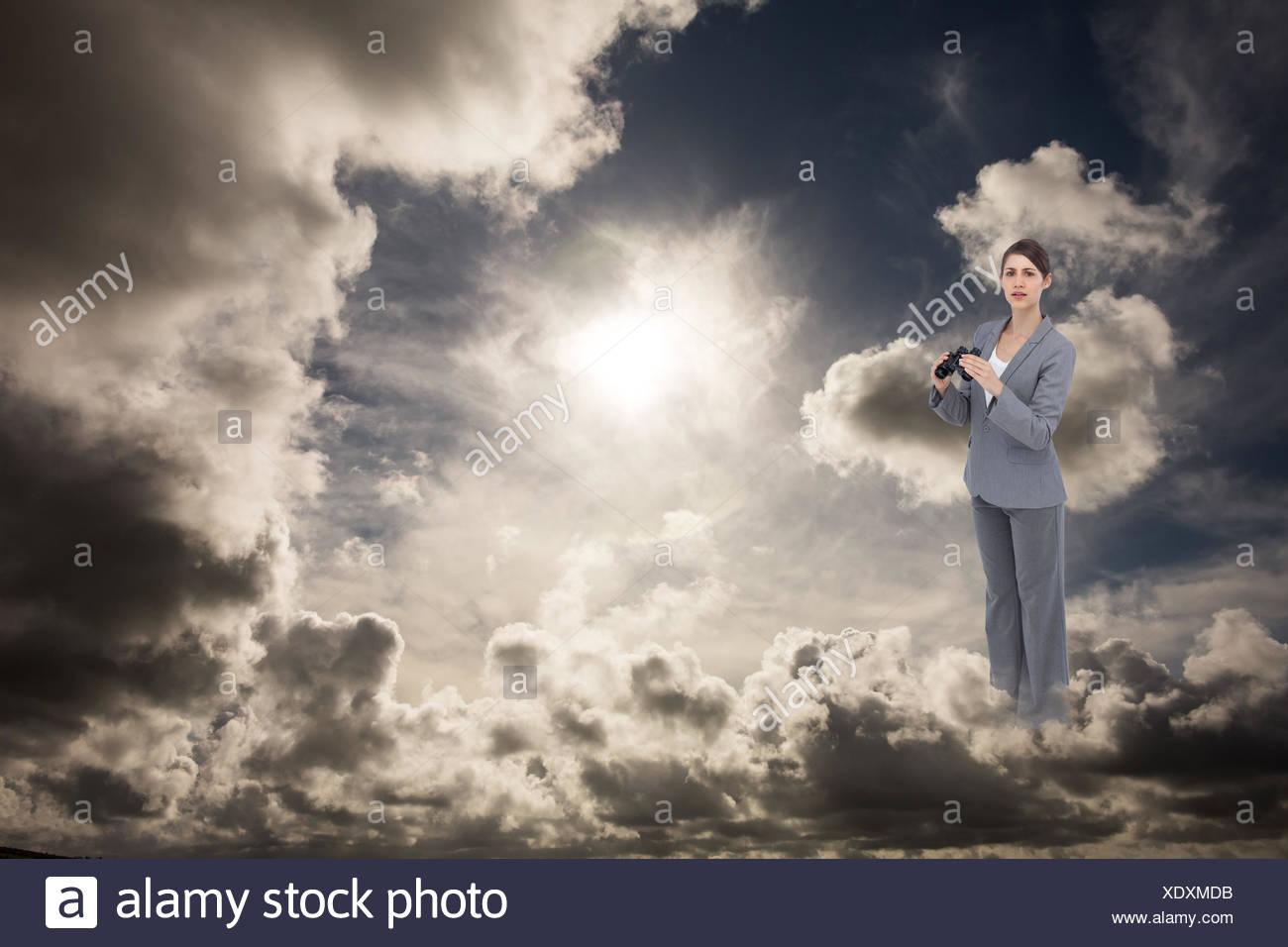 Composite image of businesswoman posing with binoculars Photo Stock
