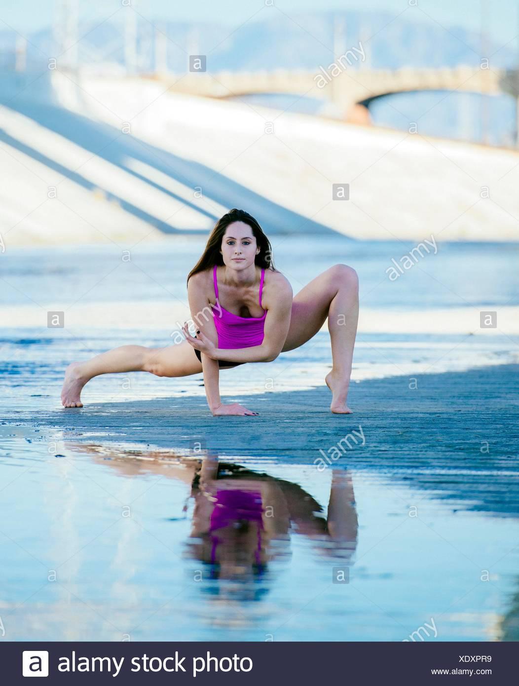 Vue avant du danseur, ouvrir les jambes, en appui sur les mains, se pencher en avant, en équilibre, looking at camera, Los Angeles, Californie, USA Photo Stock