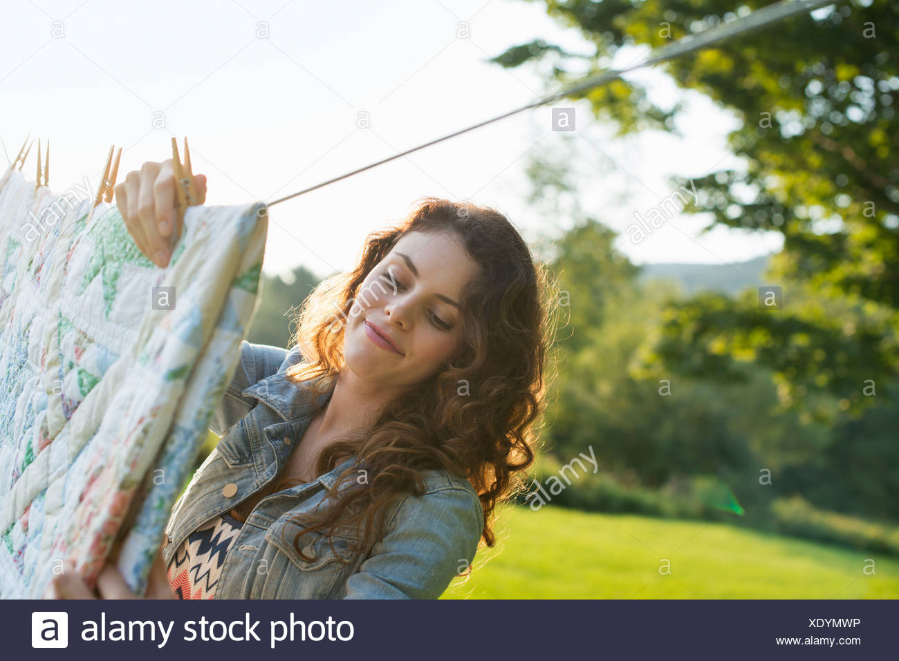 Une femme étendre le linge sur l'étendoir, dans l'air frais. Photo Stock