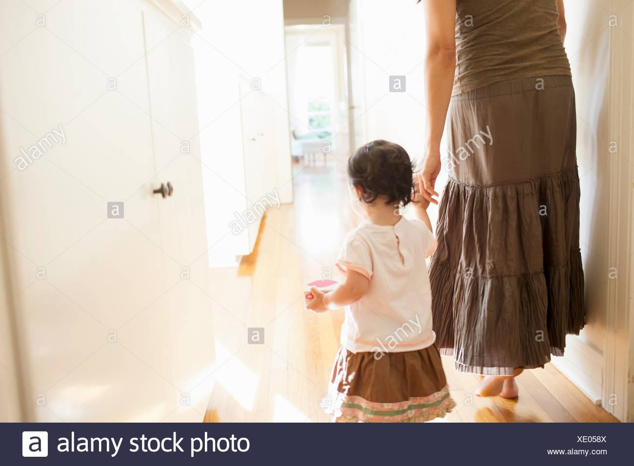 Vue arrière de mother holding baby's hand Photo Stock
