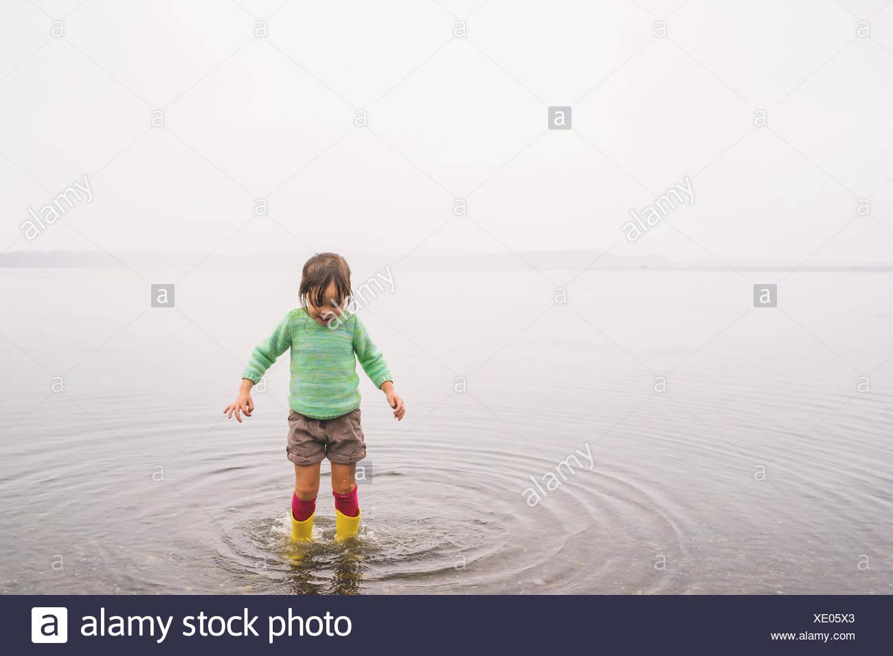 Girl en eau peu profonde, faisant des ondulations Photo Stock
