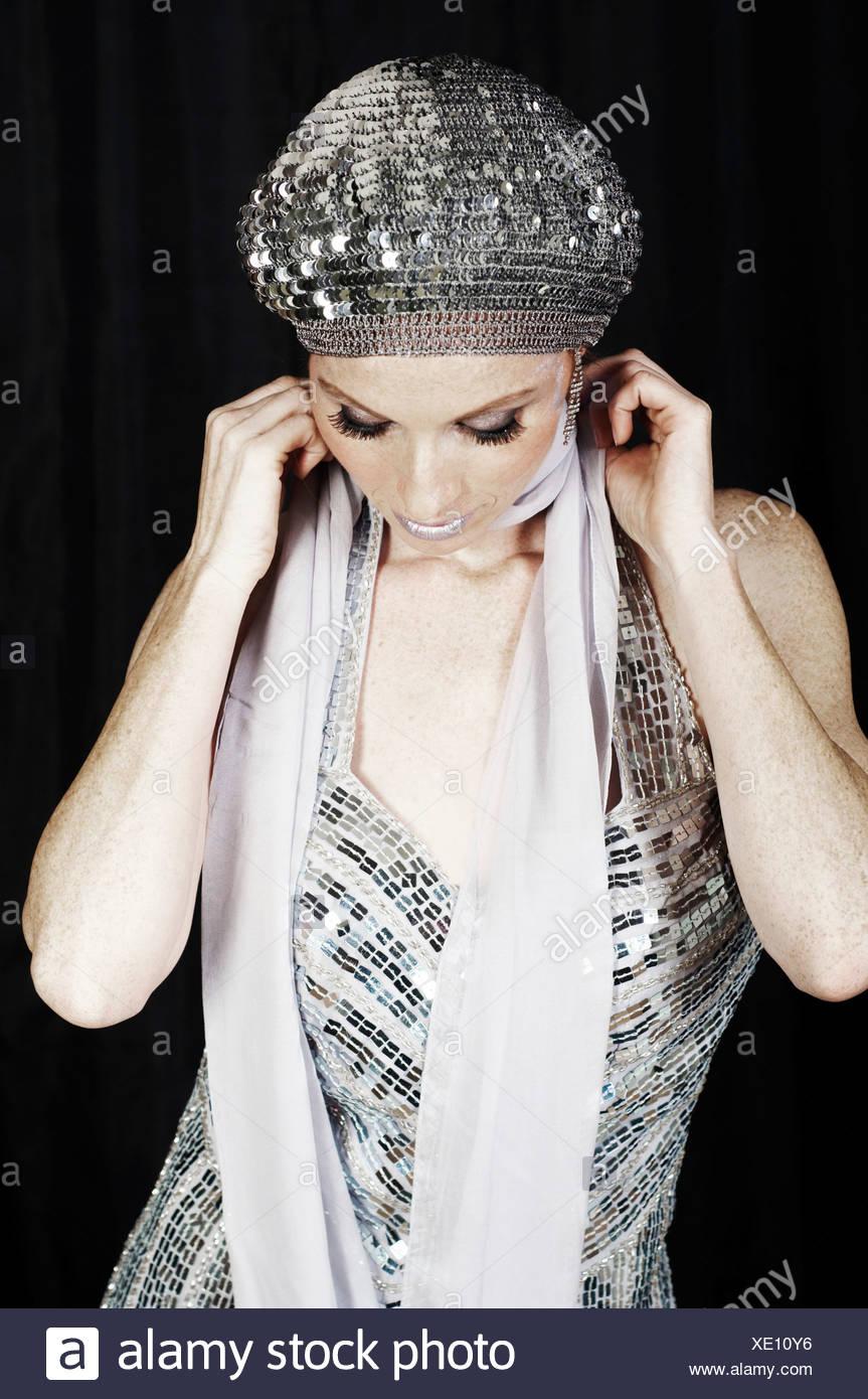 Jeune femme en robe de soirée argent avec cap Photo Stock c0fc40069ec6