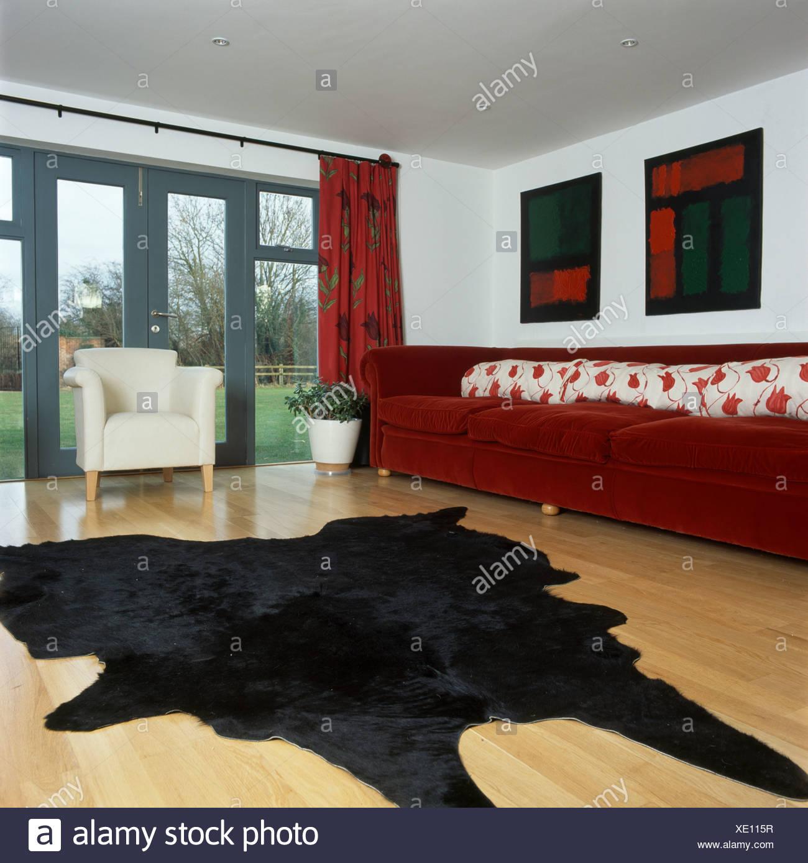 Faux Noir Couverture De Peau Animale Sur Parquet Dans Salon Moderne Avec De  Long Canapé Rouge Et Portes Fenêtres
