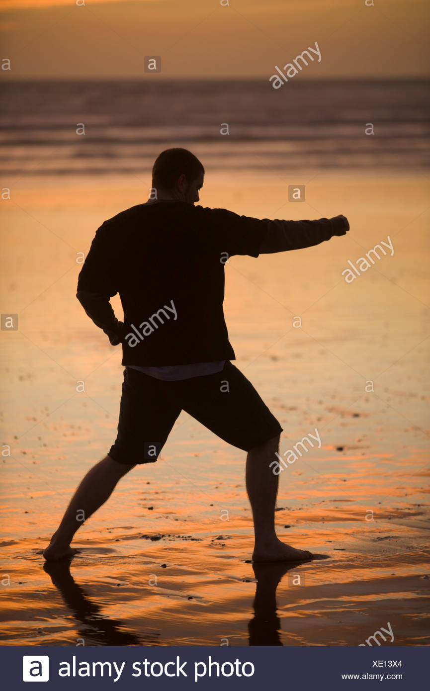 L'une des pratiques des adultes sur la plage de taekwondo au coucher du soleil à Morro Bay, en Californie. Photo Stock
