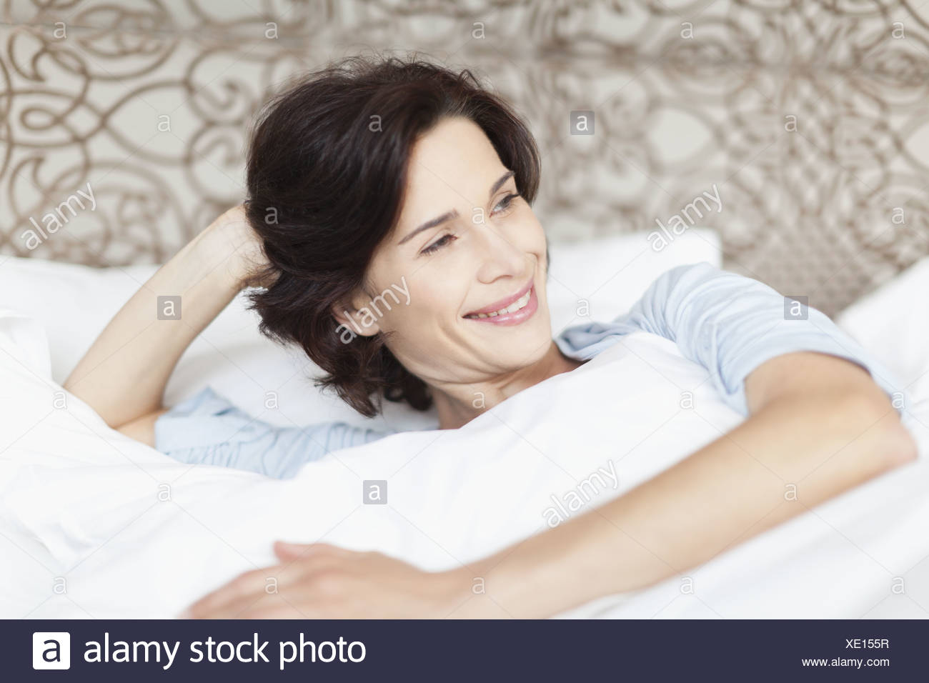 Smiling woman sitting up in bed Photo Stock
