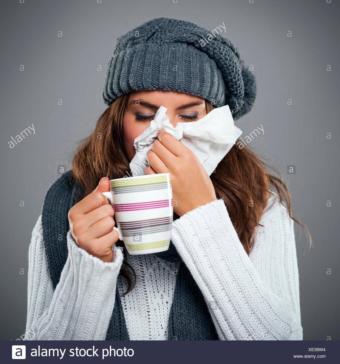 Jeune femme ayant la grippe et s'être mouché le nez au mouchoir Debica, Pologne Banque D'Images