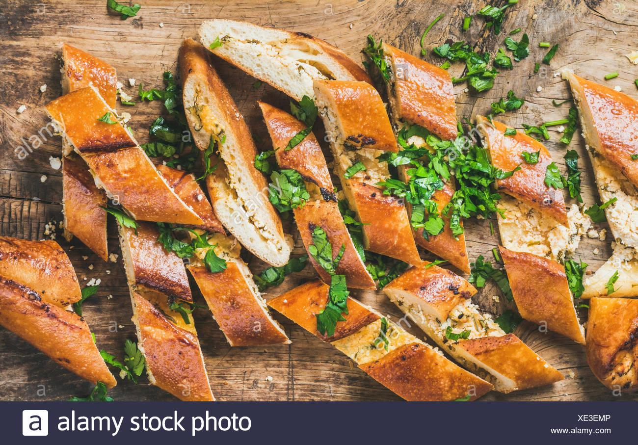 Close-up of oriental turc pide pizza avec du fromage et des épinards hachés en tranches sur fond de bois rustique, vue du dessus Photo Stock