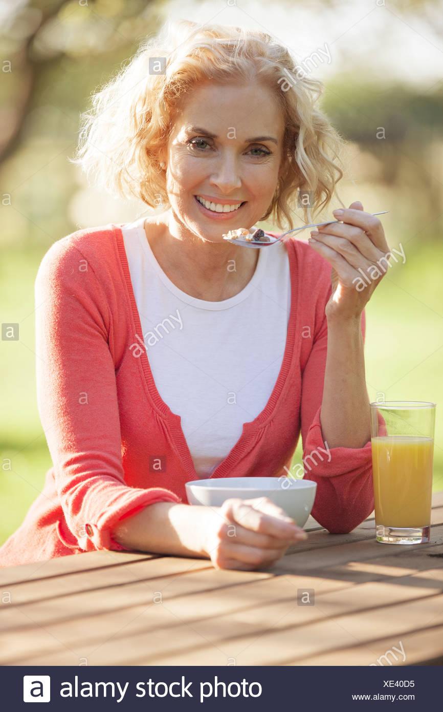 A mature woman sitting manger des céréales pour petit déjeuner Photo Stock