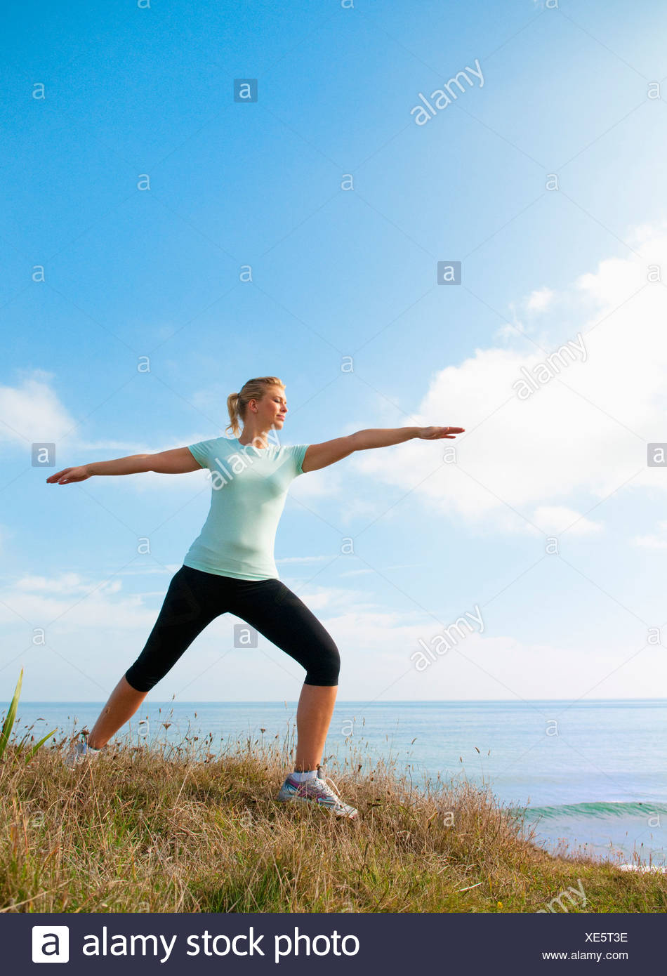 Mid adult woman stretching sur falaise, Thurlestone, Devon, UK Photo Stock