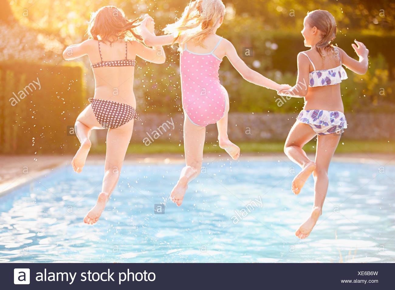 Groupe de jeunes filles, jouant dans une piscine extérieure Photo Stock
