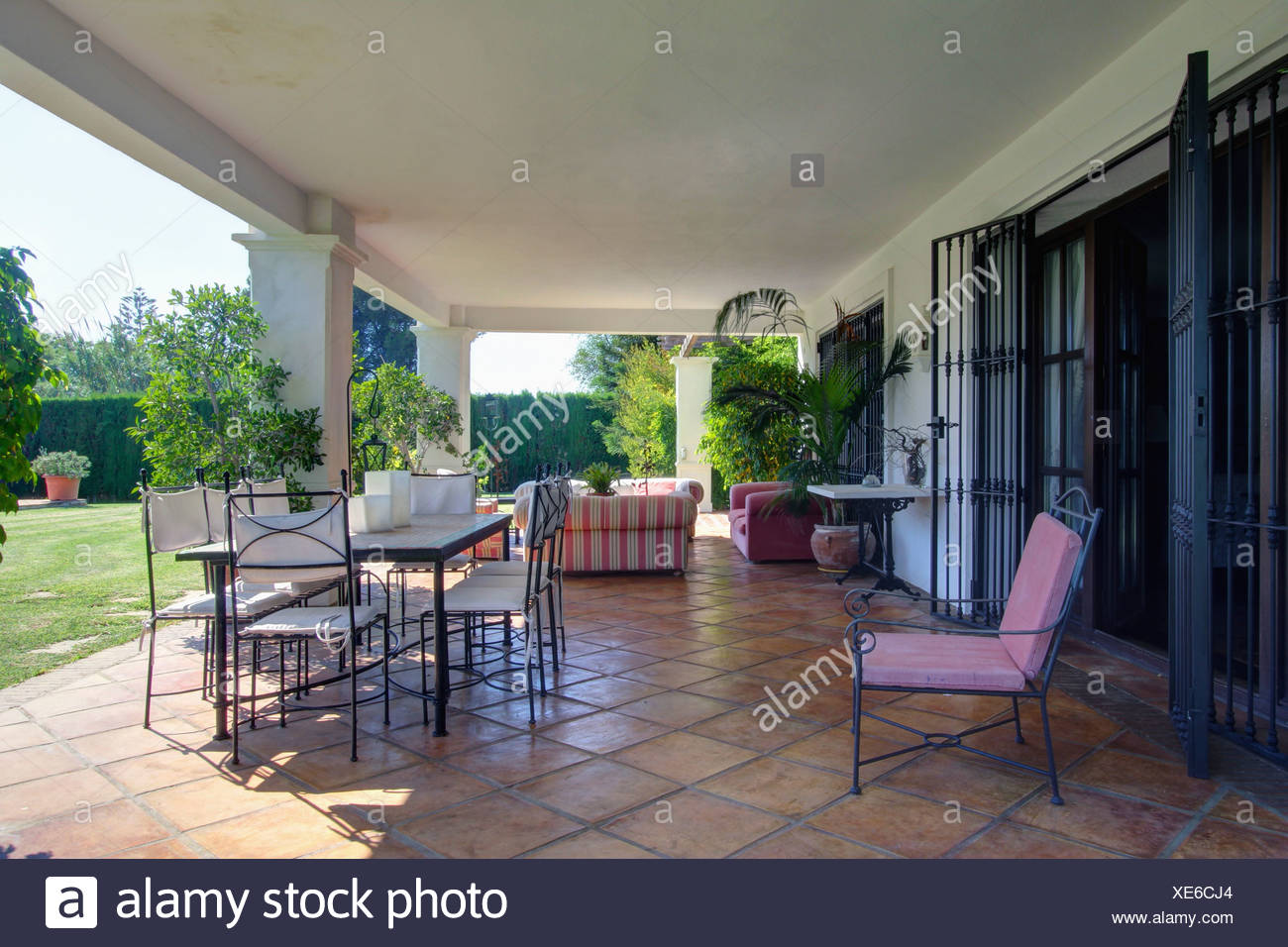 Veranda Metal Et Verre chaises et table en métal sur un sol en terre cuite