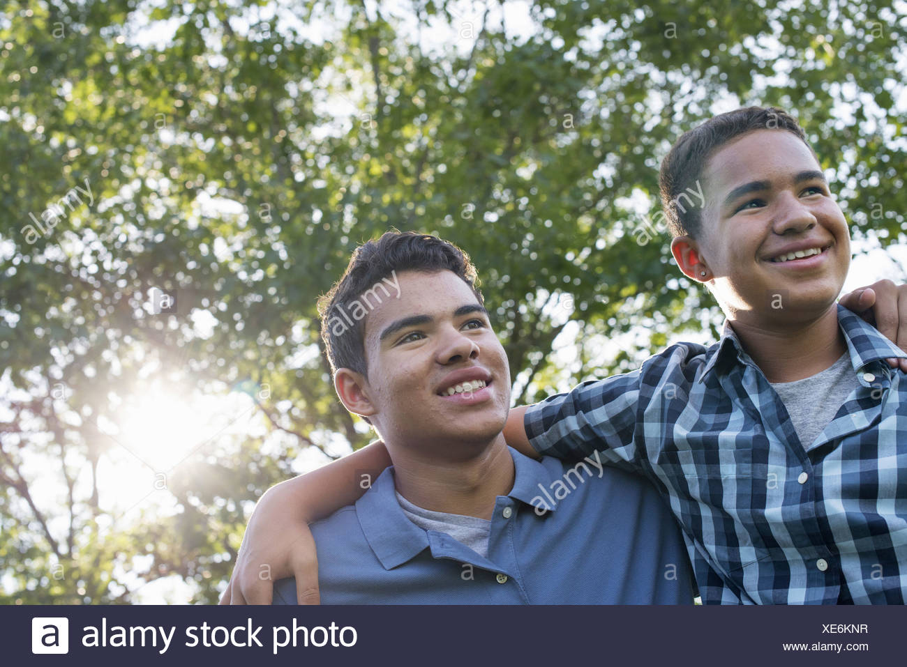 Deux jeunes hommes à l'extérieur l'un avec son bras autour des épaules de l'autre Photo Stock