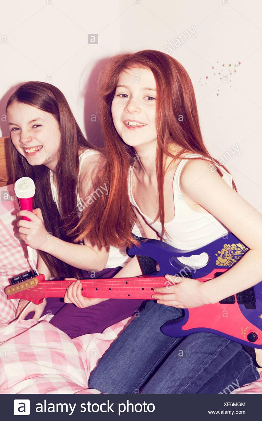 Deux jeunes filles jouent de la guitare et chanter au micro dans la chambre Photo Stock