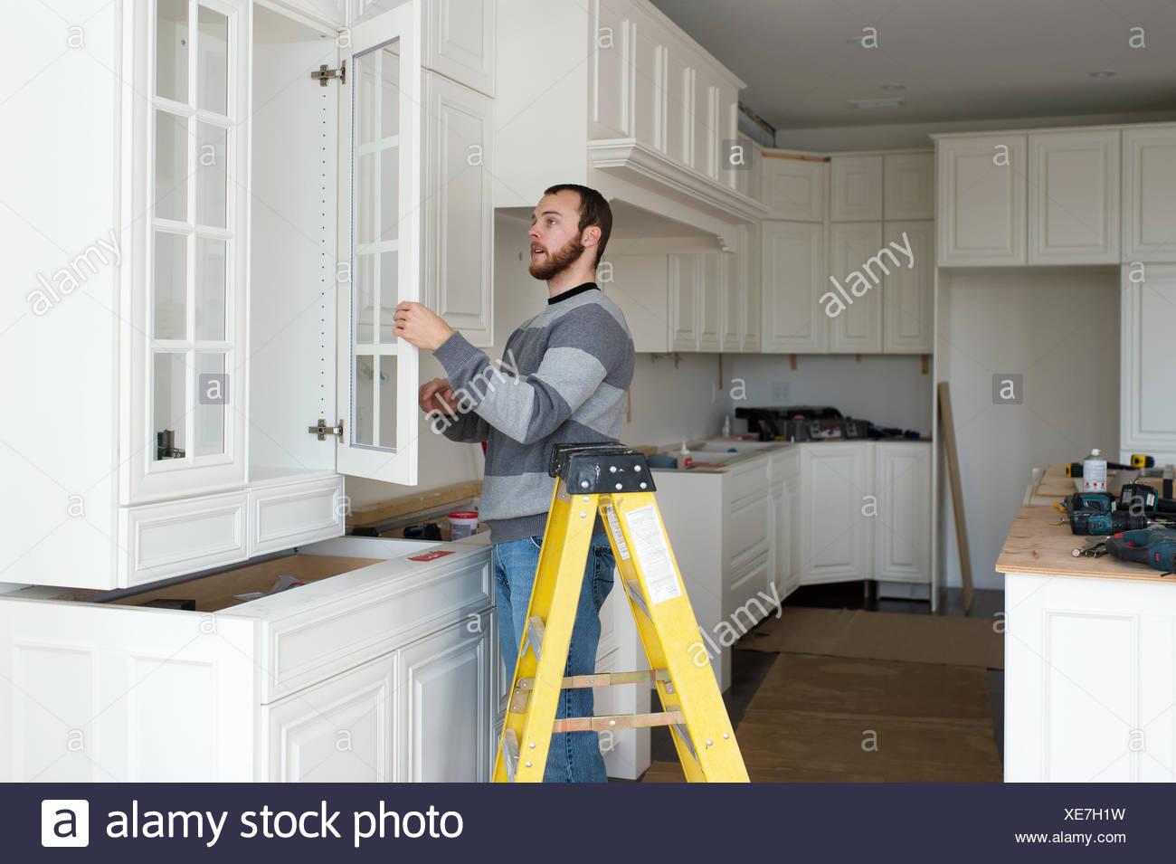 Carpenter l'installation d'armoires de cuisine Photo Stock