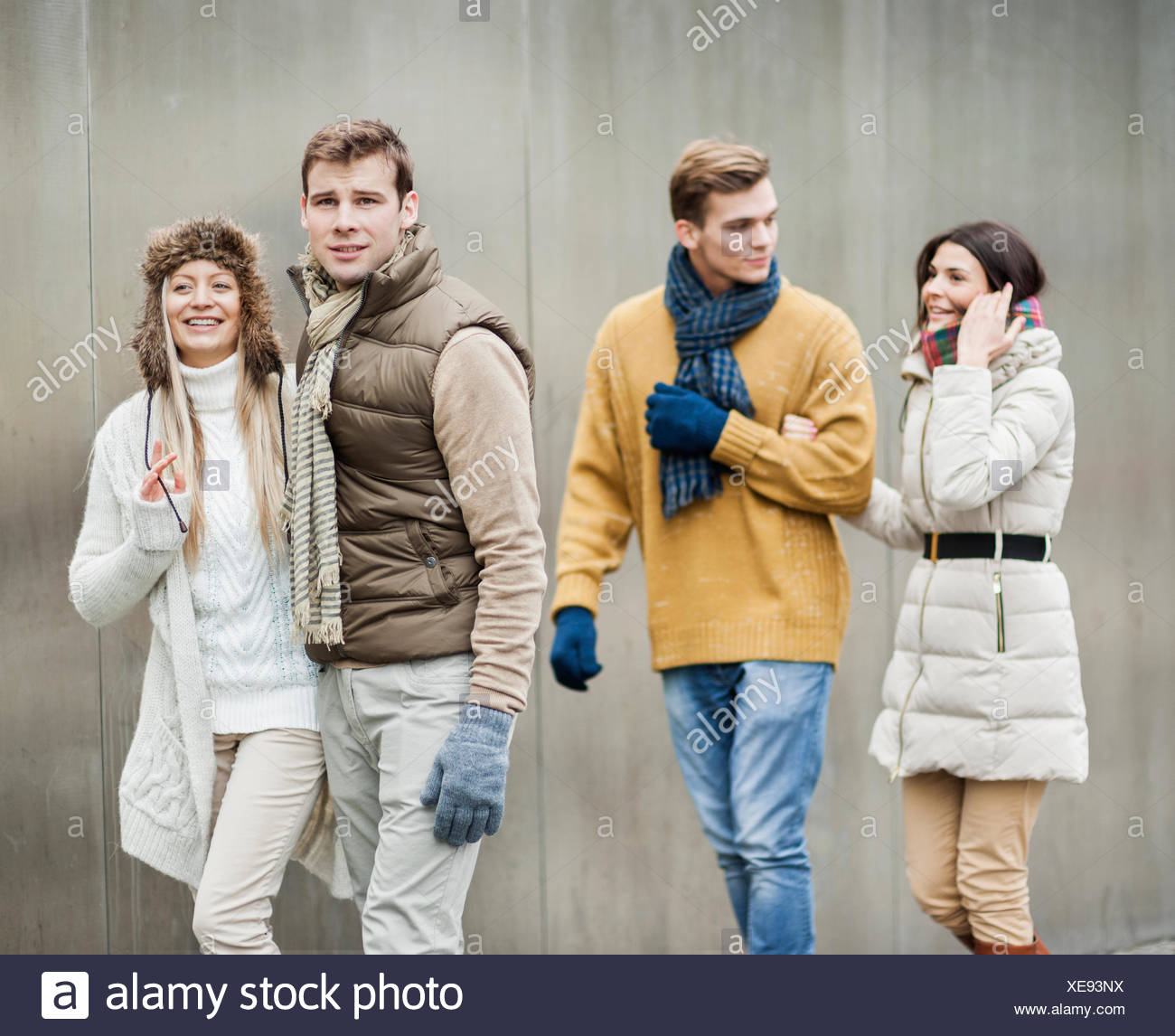 Smiling young couples walking against wall Photo Stock