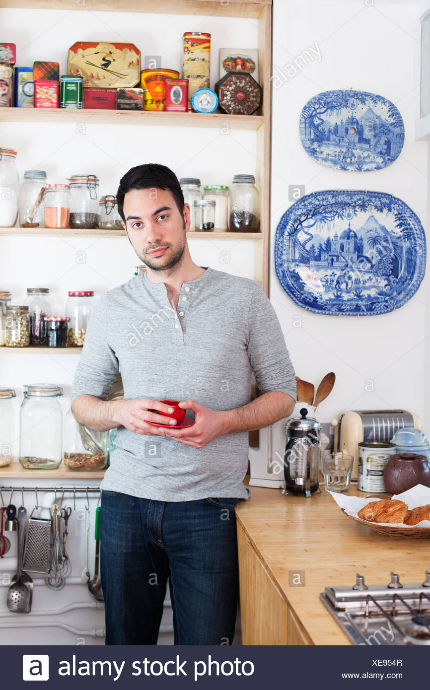 Mid adult man standing in kitchen holding Coffee cup Photo Stock