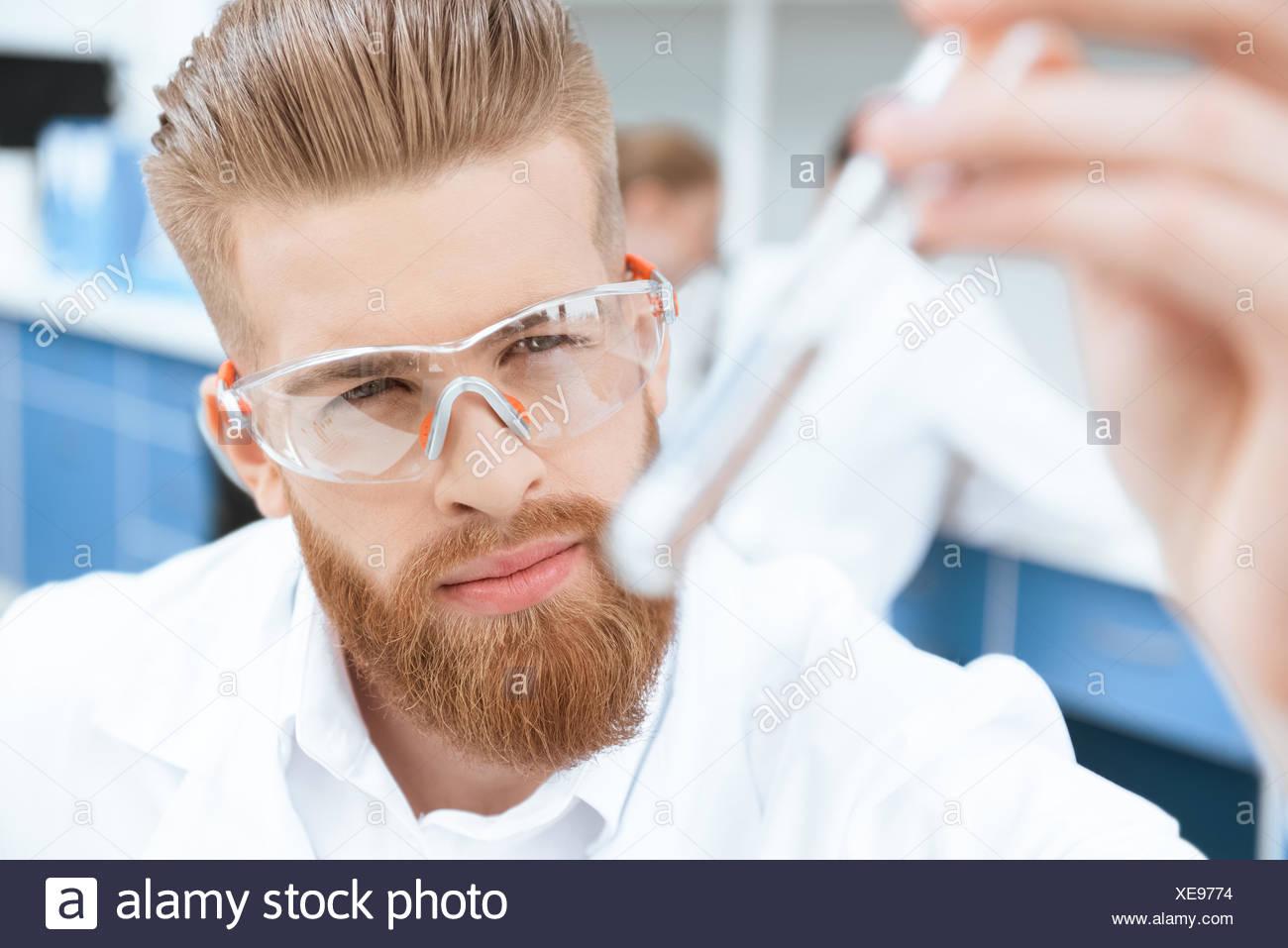 Vue rapprochée de chimiste barbu à lunettes de protection inspection test tube in lab Photo Stock