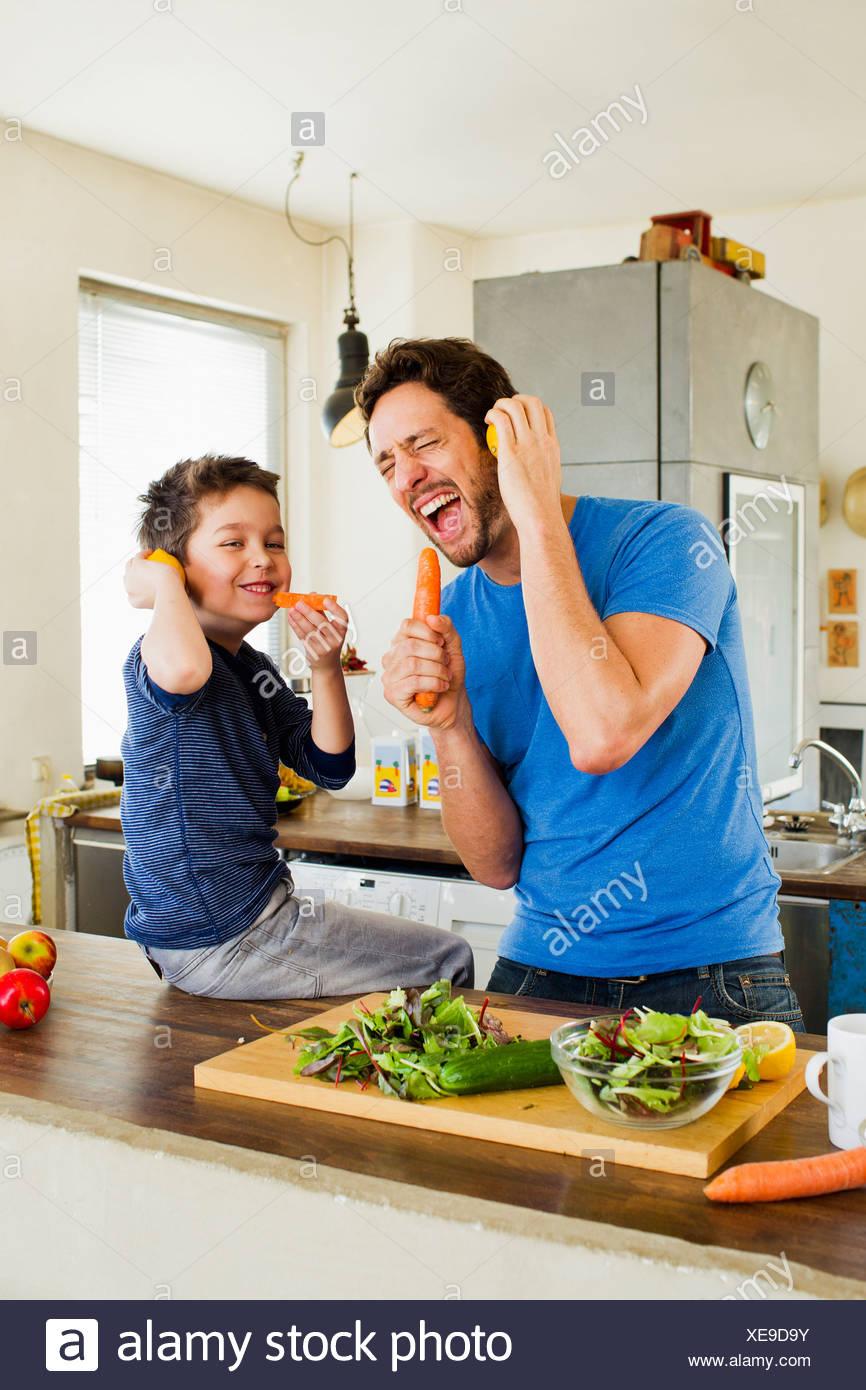 Le père et le jeune fils de chanter dans les microphones de carotte Photo Stock