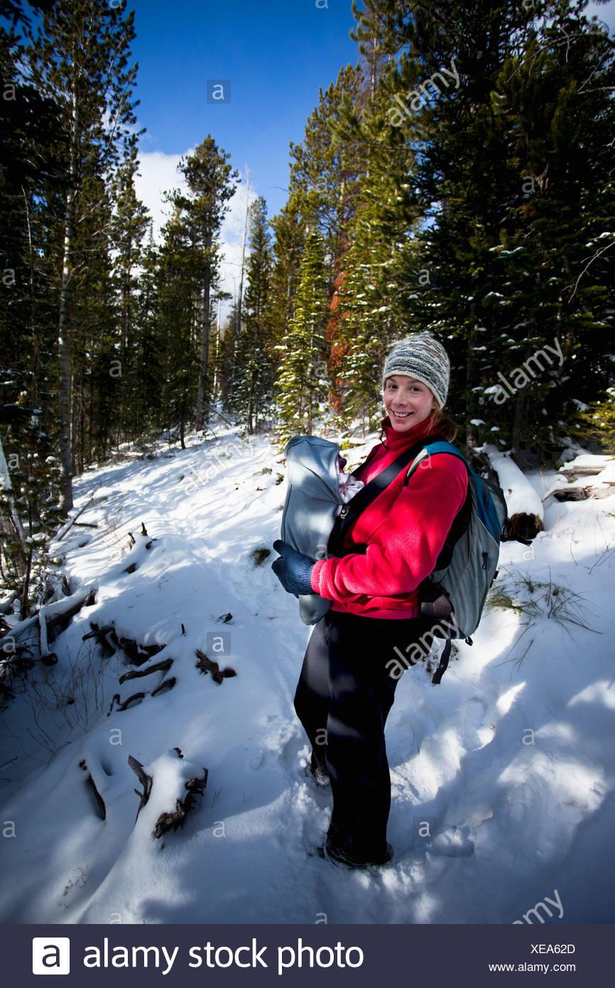 Mère et bébé nouveau-né dans un sac ventral sur un sentier de randonnée de la neige en hiver, Bitterroot Wilderness, Montana. Photo Stock