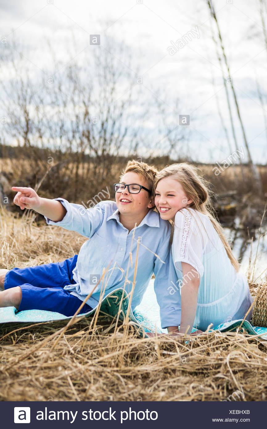 La Finlande, l'Aanekoski, Amerique, Girl (12-13) and boy (12-13) assis sur une couverture à l'extérieur et à l'écart Photo Stock