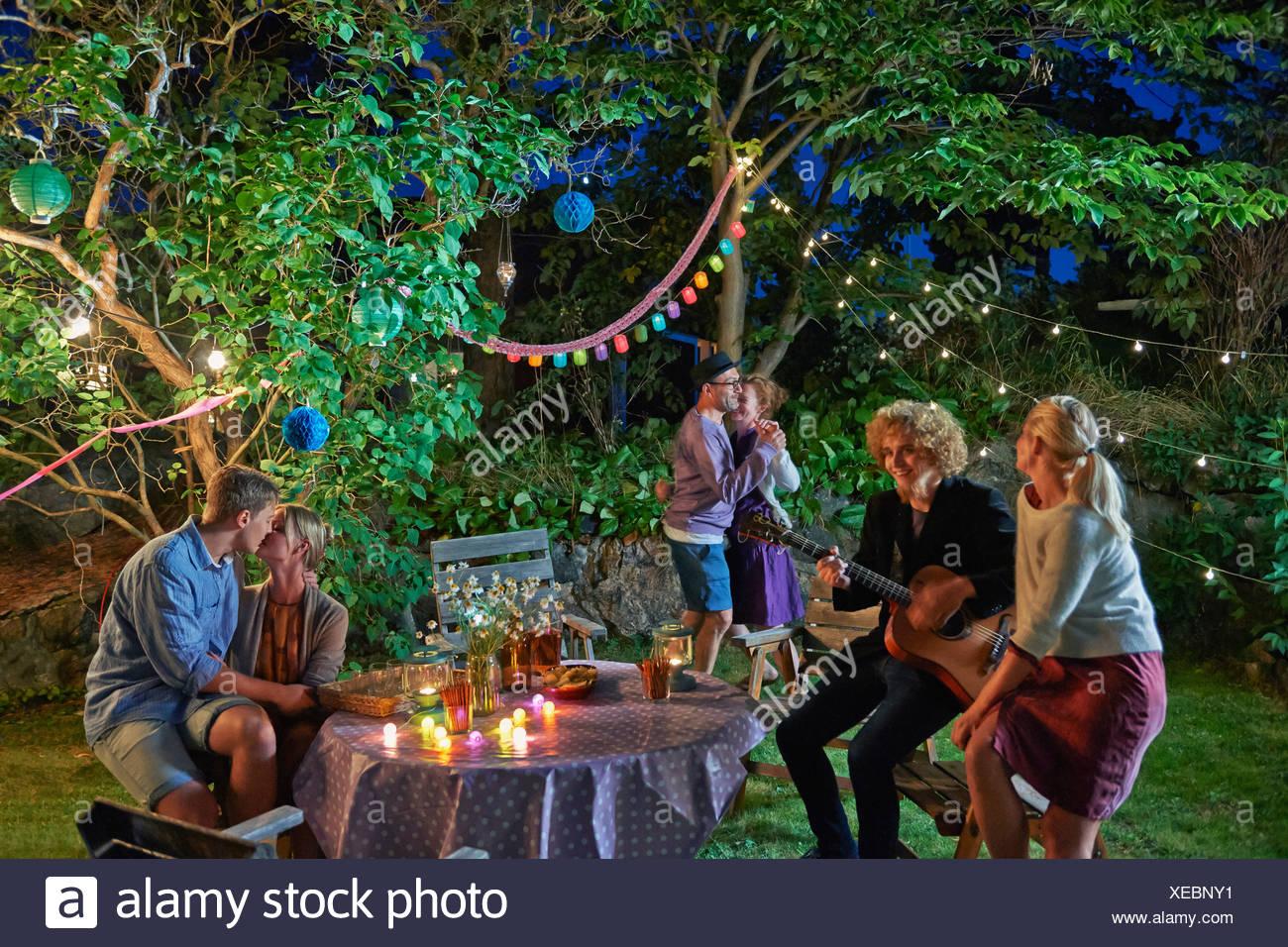 Trois couples having fun at garden party at night Photo Stock