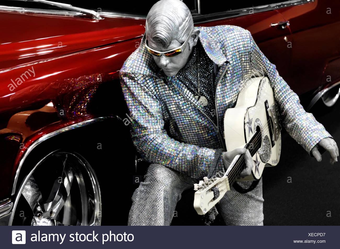 Elvis d'argent avec une guitare à genoux près d'une voiture classique rouge, d'interprètes Peter Jarvis de Toronto, Ontario, Canada Photo Stock