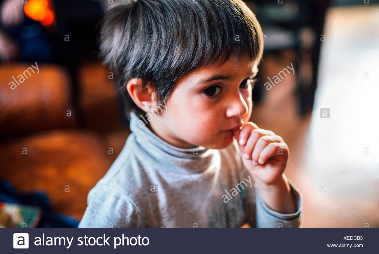 Portrait de petit garçon avec doigt dans sa bouche Photo Stock