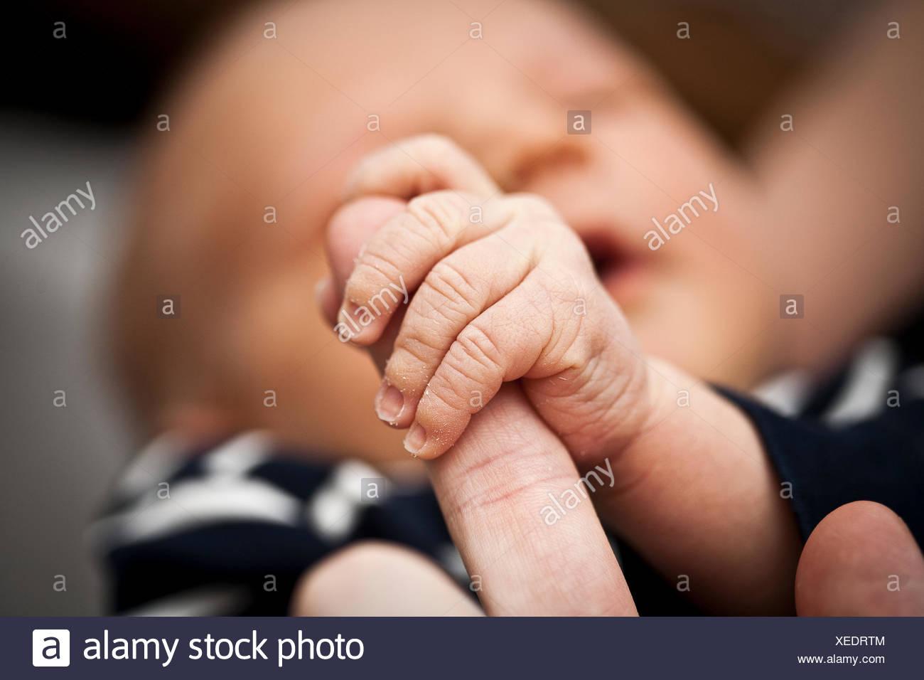 Boy (0-1 mois) maintenant le doigt du père Photo Stock
