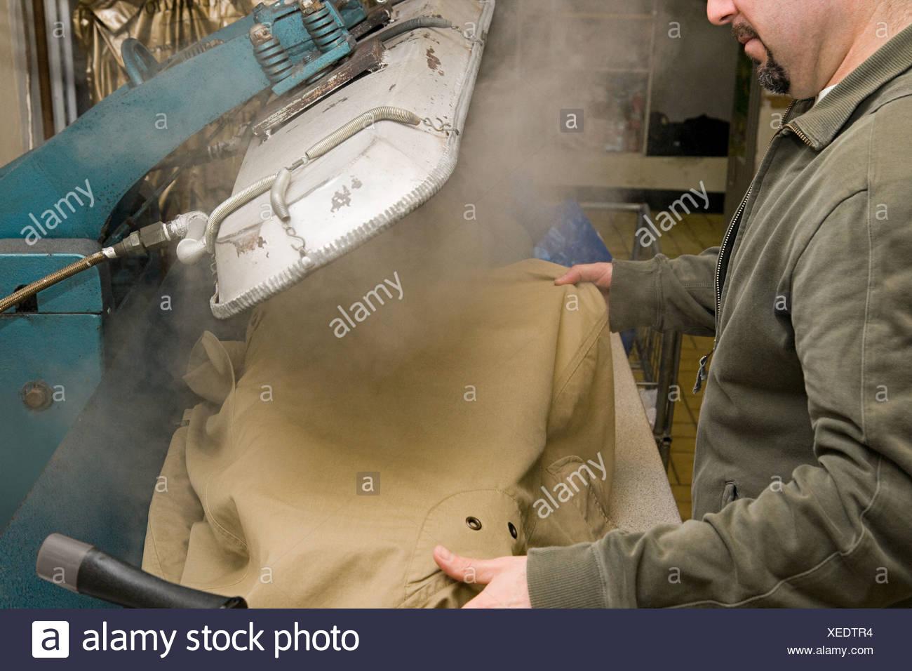 L'homme à l'aide d'une presse à pantalons Photo Stock