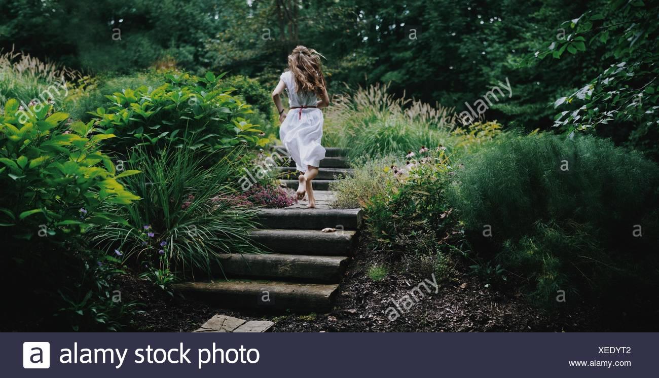 Vue arrière du young woman running up étapes dans un jardin Photo Stock