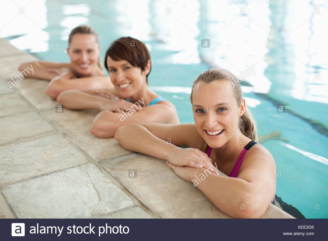 Portrait of smiling women leaning on edge of swimming pool Photo Stock