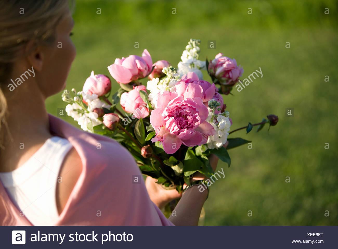 Femme portant un bouquet de fleurs, Fejan, archipel de Stockholm, Suède. Banque D'Images