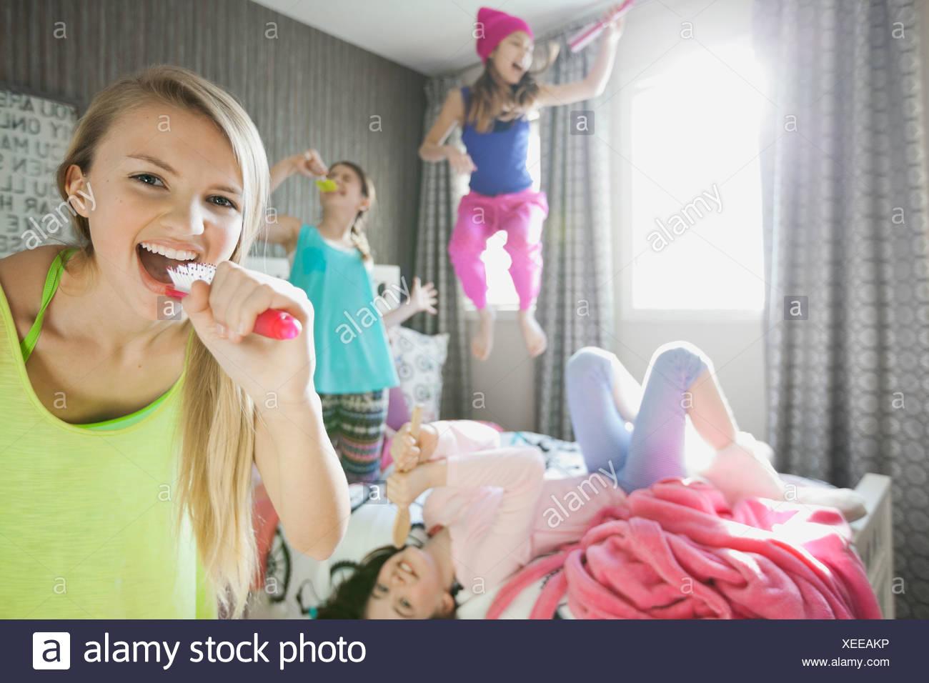 Girl singing into hairbrush at slumber party Photo Stock