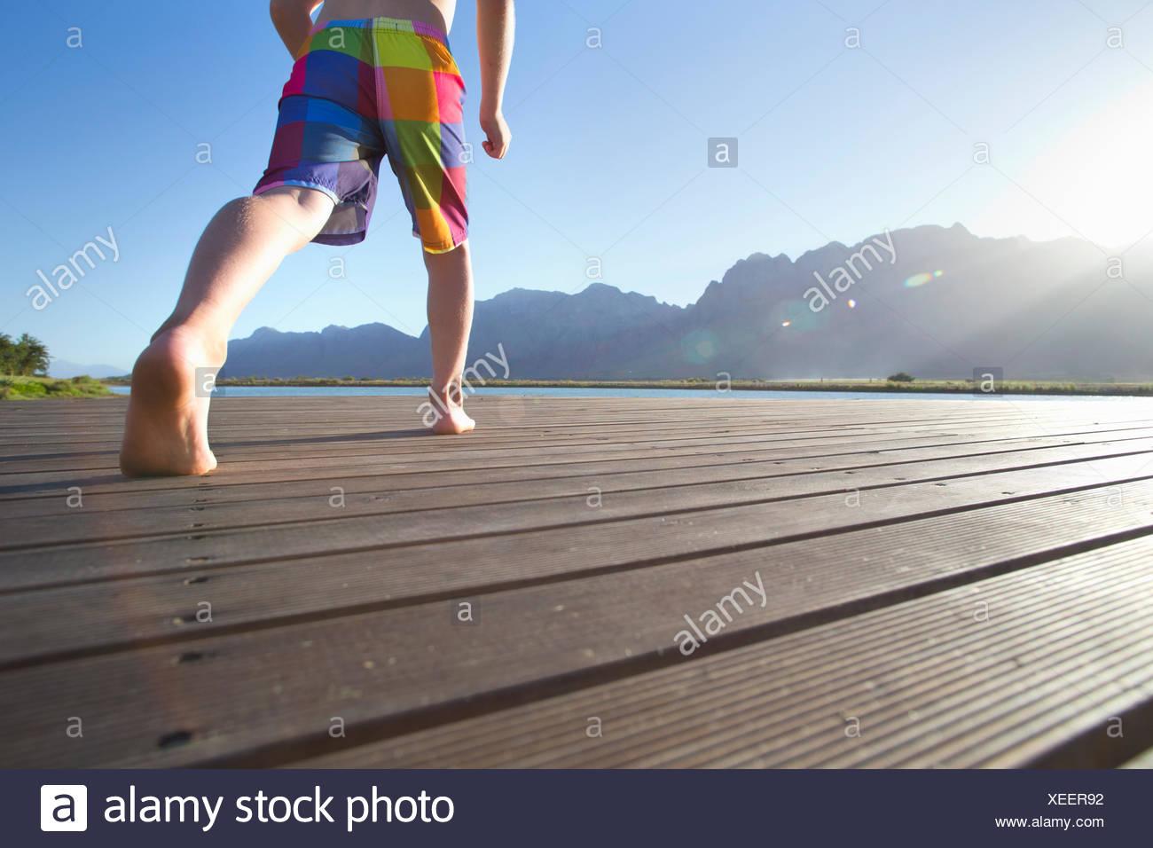 Boy running à sauter dans un lac d'une jetée Photo Stock