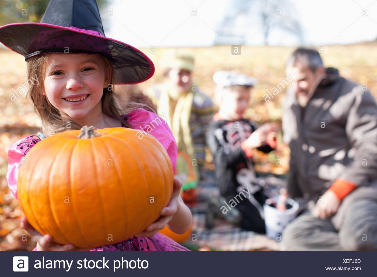 Jeune fille dans un costume d'Halloween citrouille holding Photo Stock