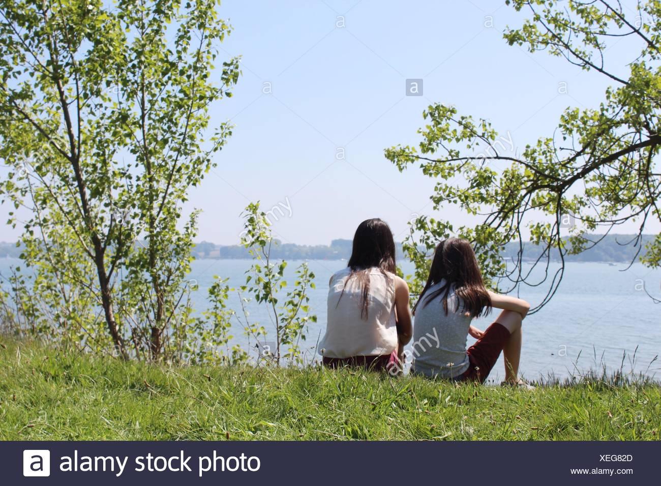 Deux filles de s'asseoir près de river Photo Stock