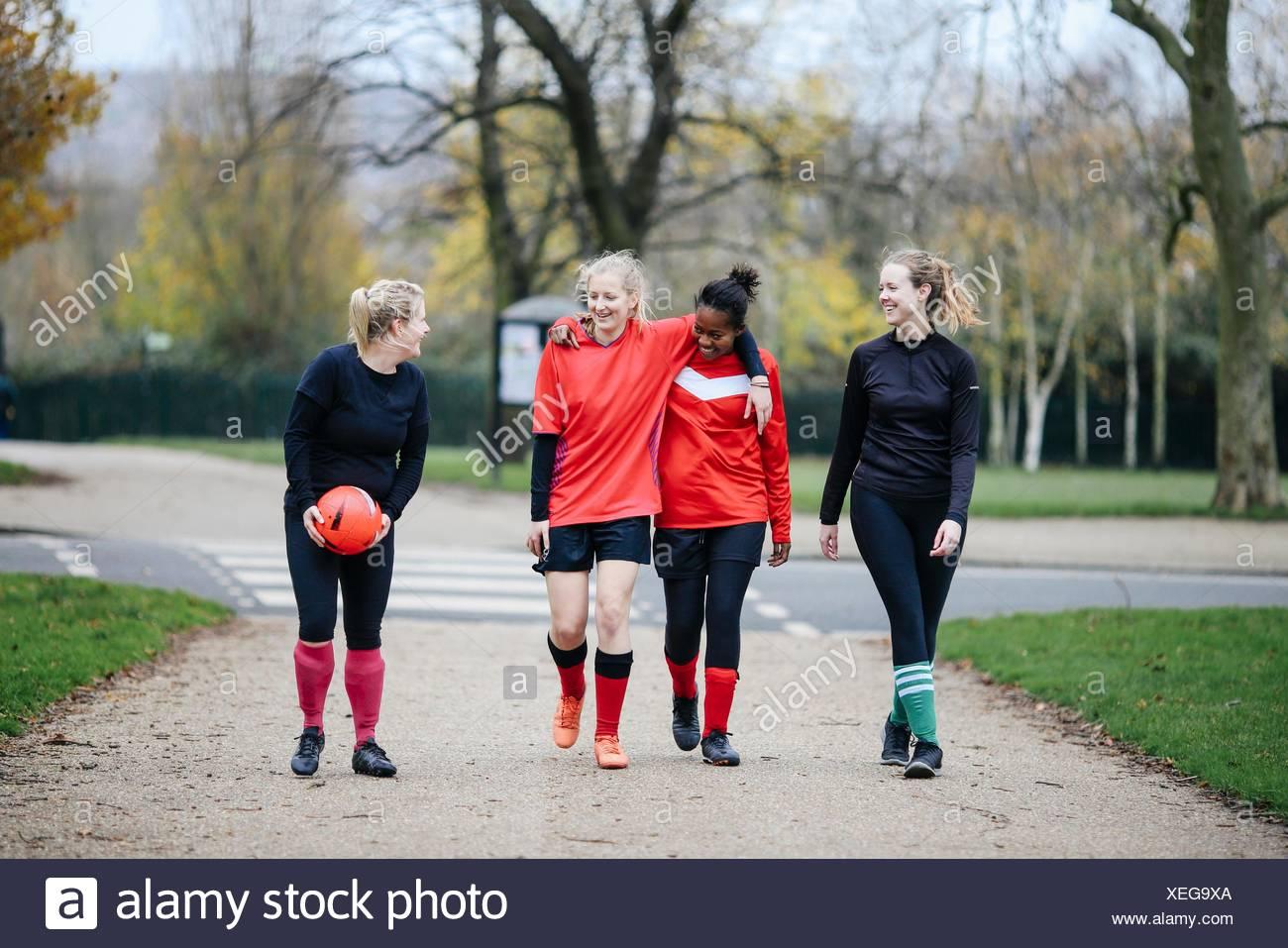 Les joueurs de soccer féminin en route pour jouer au football dans le parc Photo Stock
