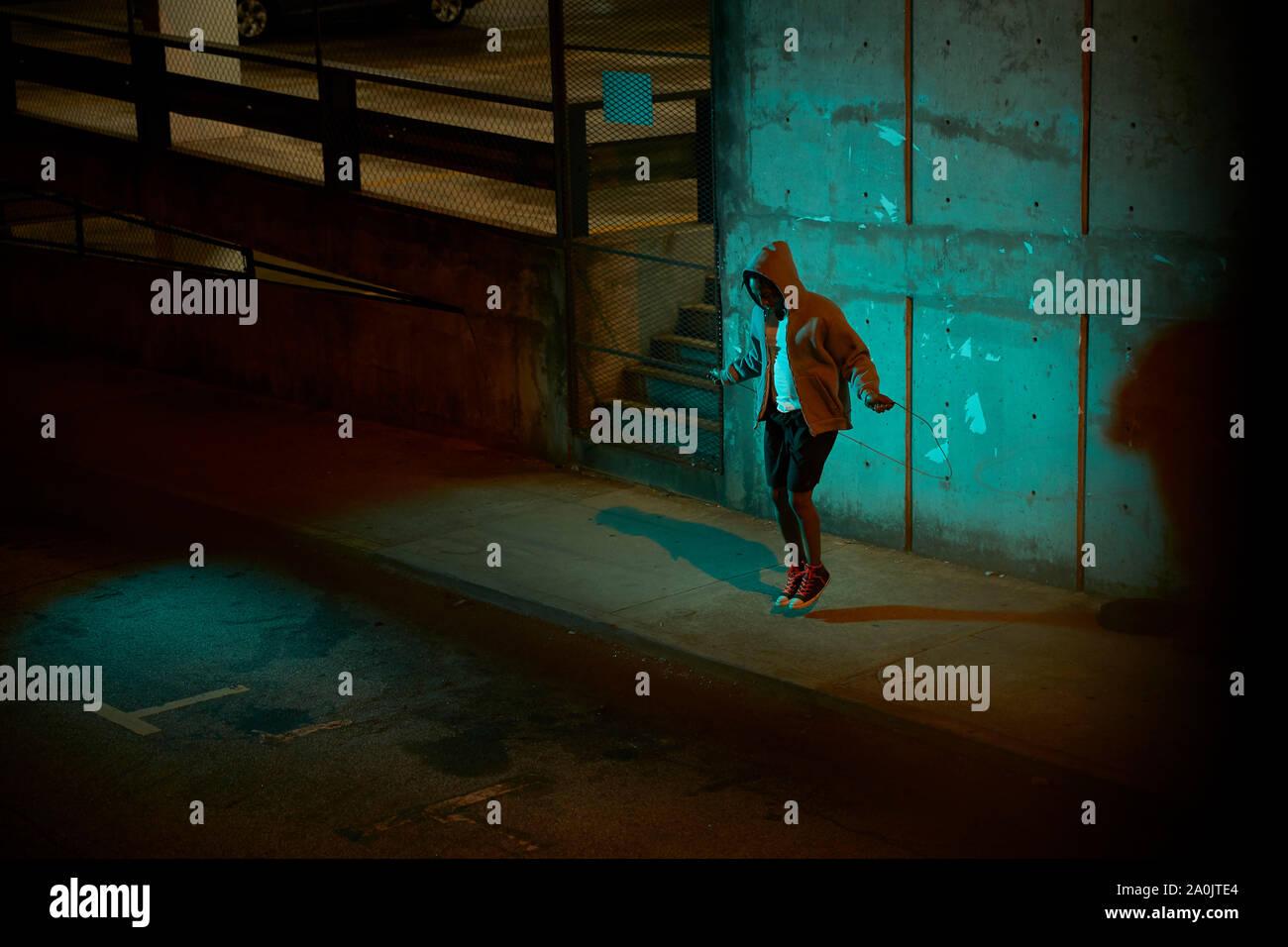 Afro-americano di uomo che indossa hoodie salto con la corda di notte Foto Stock