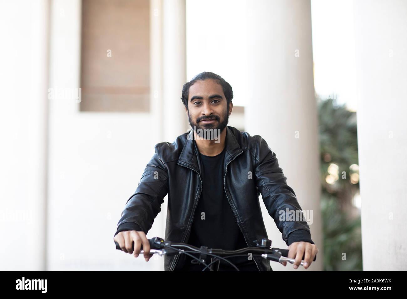 Giovane uomo percorsi in bicicletta in città Foto Stock