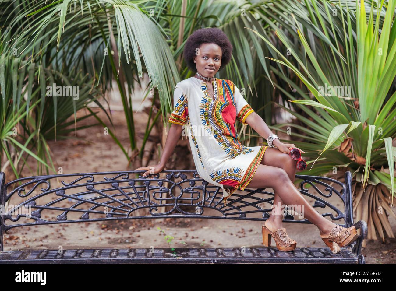 Giovane donna in posa su un banco di lavoro tra piante tropicali Foto Stock