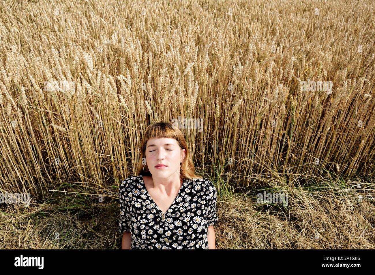 Ritratto di giovane donna con gli occhi chiusi rilassante nella parte anteriore del campo di grano Foto Stock